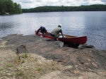 Fritz and David get back in the canoe after exploring a rocky campsite.