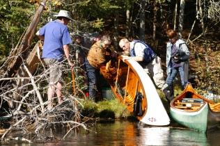 WCHA members help empty water from an overturned canoe.