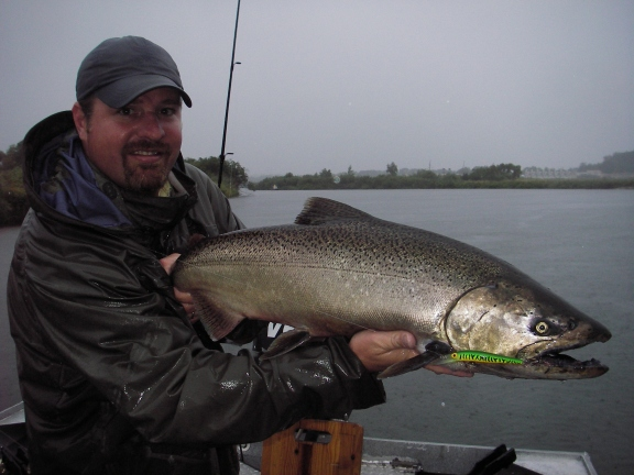 Jay Koehler holds up a rainy day chinook salmon caught on the Manistee River. Photo by Howard Meyerson