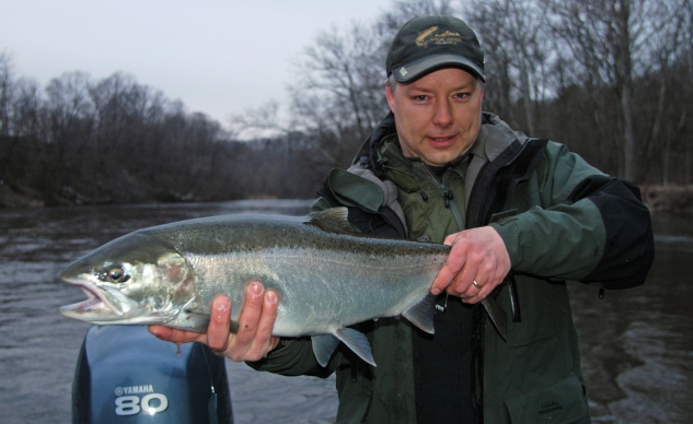 Aaron Kamphuis, of Rockford, hoists up a nice silver steelhead caught on the Muskegon River.