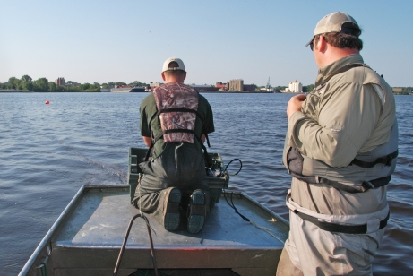 DNR summer staffer, Tanner Sommerfeld (left)  and Brandon Harris set nets on Muskegon Lake in an attempt to collect sturgeon for tagging.  Photo: Howard Meyerson