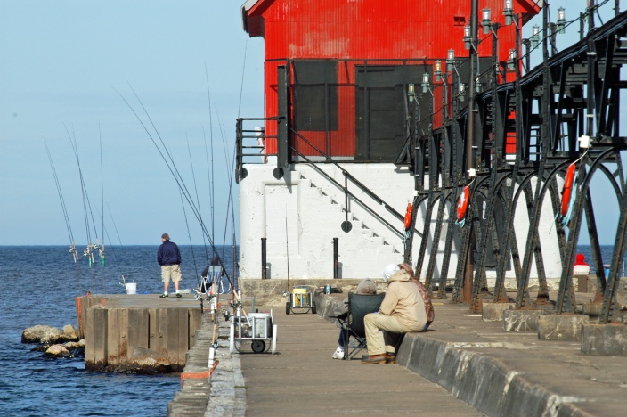 Anglers on the Grand Haven pier wait for a bite. Some say fishing has been been slow, but some larger salmon were caught earlier this spring. Photo: Howard Meyerson