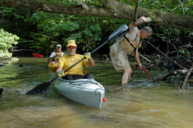 Association members Bill Hoenes, center, and Bill McKinney, back, paddle past Dick Curtis while he works to clear a segment of the water trail on the Black River. Photo: Howard Meyerson