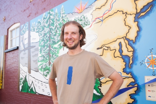 Luke Jordan enjoys the Trail Town celebration recently held in Lowell, Michigan where a new NCT mural was unveiled behind him. The blue blaze on his T-shirt is similar to the markings found along the trail letting hikers know they are on the right path. Photo Brandon Mulnix
