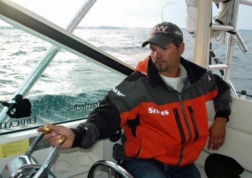 Captain Brian Butts pilots his  boat through bouncing seas hunting for big salmon on Lake Michigan. Photo: Howard Meyerson