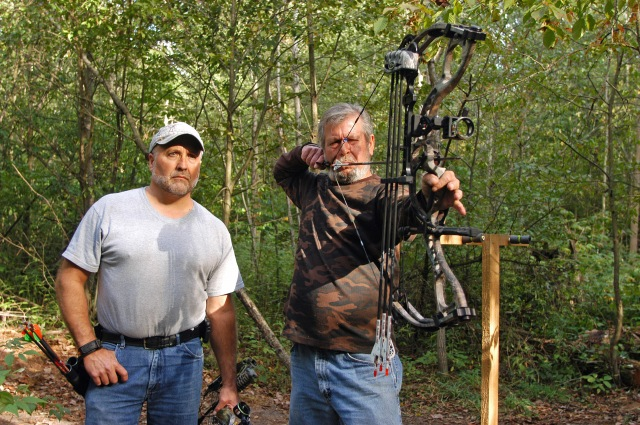 Mike Niva (left) looks over Mike Kotecki's shoulder as he practices for the opening of archery deer season and draws a bead on a 3-D target at the Fruitport Conservation Club. Photo: Howard Meyerson