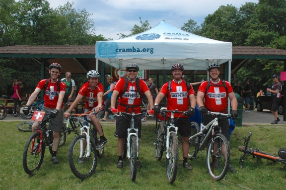 Five mountain bike patrol members in front of the CRAMBA (Clinton River Area Mountain Bike Association) tent at the group's 2013 Girls on Trails Clinic held at River Bends Park in Shelby Township Pictured left to right: Ken Becker, Norbert Skorupski, Aaron Burgess, JeremyVerbeke. Photo: Clinton River Area Mountain Bike Association.