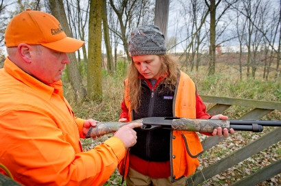 Trish Taylor recieves some instruction from Scott Brosier while shooting some skeet before the hunt. Photo: Dave Kenyon, Michigan DNR.