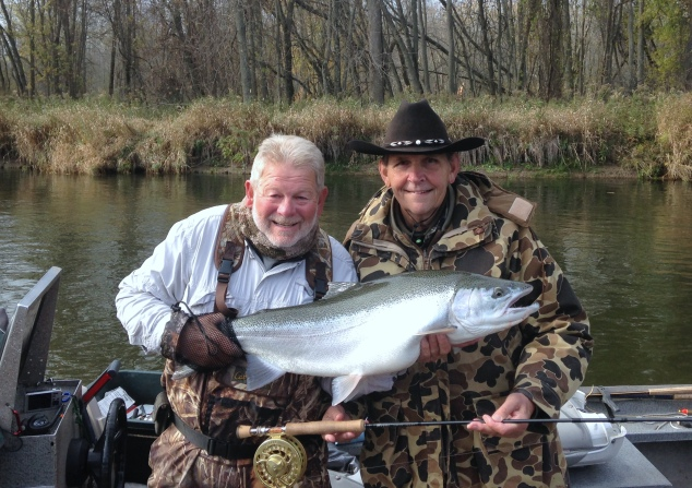 Fishing guide, Chuck Scribner (left) helps his client and friend, Bill Fuhs hold up the 38-inch steelhead Fuhs caught on the Big Manistee River last fall. (Courtesy | Captain Chuck Scribner)