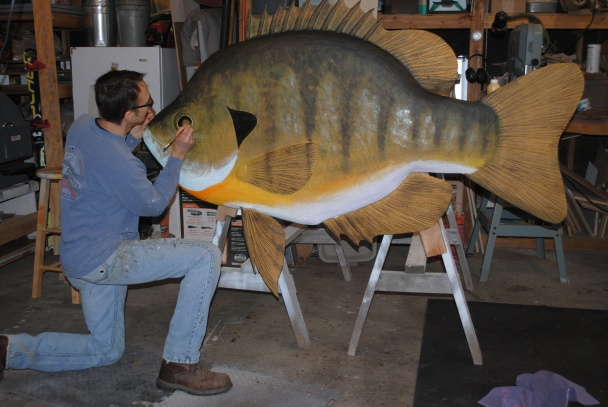 Bob Batchik works in his studio to finish painting a large bluegill wood carving for a client. (Courtesy | Bob Batchik, Sunfish Woodworks)