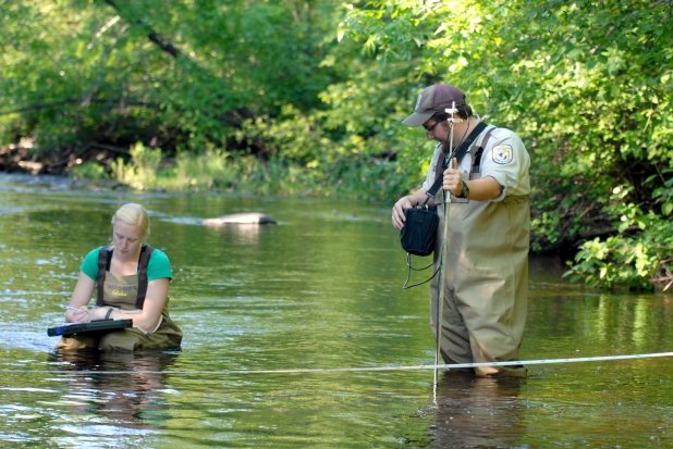 Sea lamprey researchers measure stream velocity and discharge in the Carp Lake River to determine the appropriate concentration of alarm substance to apply.  Photo: Tom Luhring, Michigan State University.