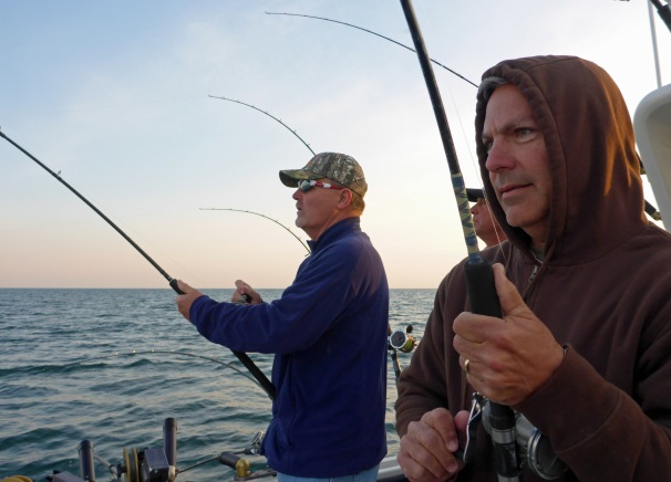 David Kostecki, from Oakville MO (left) and Stan Kostecki (right),from Defiance MO, work to reel in two salmon as Captain Russ Clark looks on. Photo: Howard Meyerso