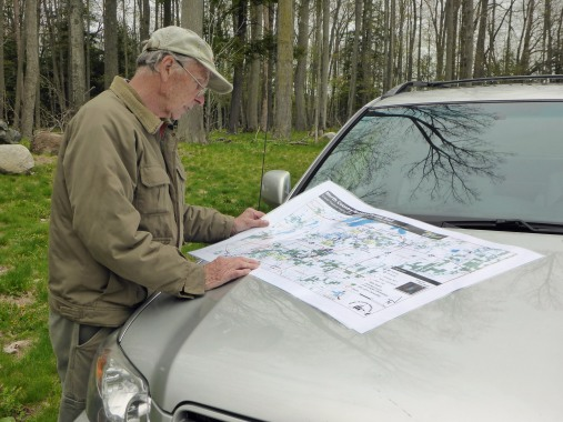 Volunteer trail builder and coordinator, Arlen Matson, looks over the map of the new trail that was soon to be posted at the U.S. 131 roadside park kiosk. Photo: Howard Meyerson.