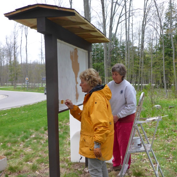 Grand Traverse Hiking Club volunteers, Deena Barshney (left) and Marilyn Hoodstraten, help paint a new trailhead kiosk for the North Country Trail. Photo: Howard Meyerson