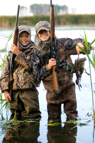 A young hunter holds up a green-winged teal, a species that sticks around longer than blue-wings. Photo: Dave Kenyon, Michigan DNR.
