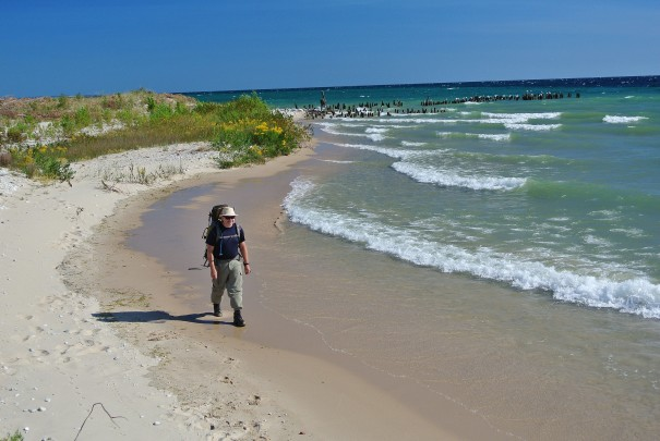 A backpacker hikes along the beach at North Manitou Island. Photo: Jim DuFresne