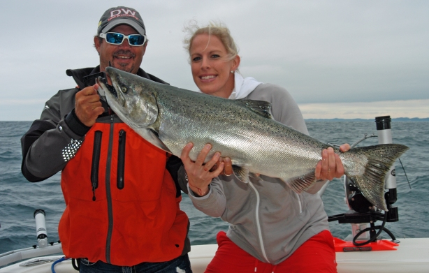 Captain Brian Butts, owner of Sea Flea Charters, helps Ashley Wiersma hold a big salmon she caught while fishing Lake Michigan in 2013. Far fewer that size were caught in 2014. Photo: Howard Meyerson