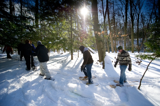 A group enjoys a guided snowshoe hike at P.J. Hoffmaster State Park where wooden snowshoes can be rented. Photo credit: Dave Kenyon, Michigan DNR