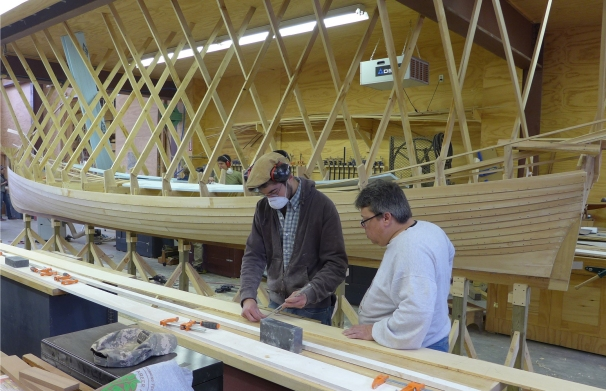 Students Ben Davant, left, and Mike Podgajski shape the final plank for the pilot gig. Photo courtesy of the Great Lakes Boat Building School.