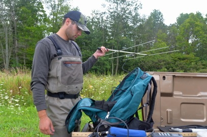 Graeme Zaparzynski uses a radio antennae to locate a brook trout in Cedar Creek that carries a tiny transmitter in its abdomen. Photo by Howard Meyerson