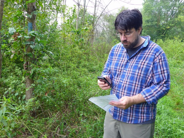 Matt Rowbotham, the cartographer for the North Country Trail Association, stops along the trail (marked by blue blazes on trees) to compare information on a paper map and the new digital map for the trail. Photo by Howard Meyerson