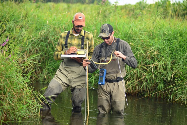 Justin Wegner, left, and Graeme Zaparzynski take ambient water temperature readings at a random spot downstream from where they located a tagged brook trout. Photo by Howard Meyerson.