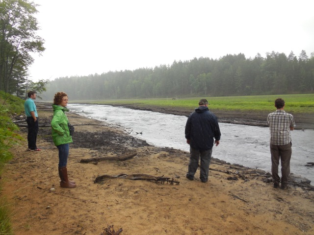 HP staff walking about halfway in old impoundment
